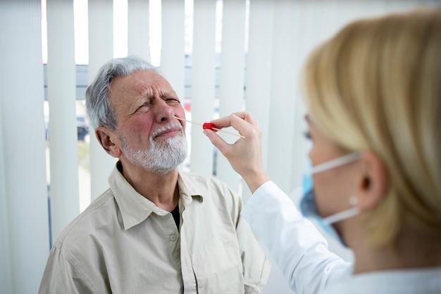 Arts die een monster van een neusuitstrijkje neemt van een oude patiënt voor een mogelijke infectie met het coronavirus.