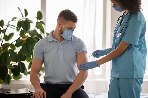 Arts die een patiënt in een kliniek vaccineert