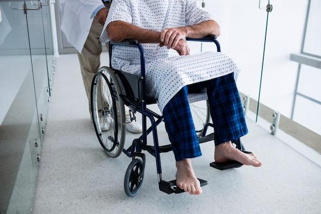 Arts die een patiënt op een rolstoel vervoert