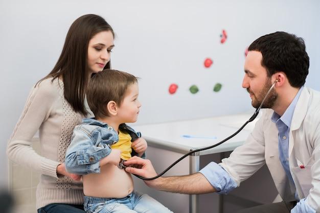 Arts die een schooljongen met zijn moeder onderzoekt op het ziekenhuiskantoor