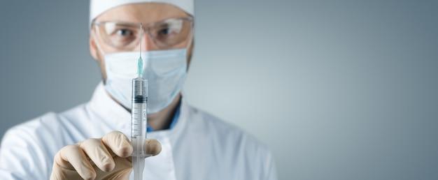 Arts die een spuit met vaccin tegen corona virus houdt.