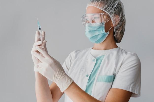 Arts die een spuit voor een vaccin houdt