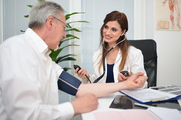 Arts die een stethoscoop en een bloeddrukmeter gebruikt om bloeddruk te controleren