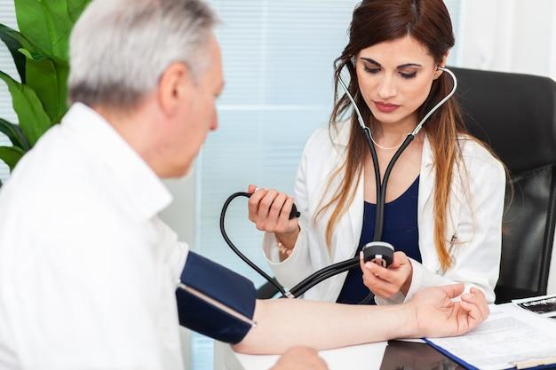 Arts die een stethoscoop en een bloeddrukmeter gebruikt om de bloeddruk te controleren