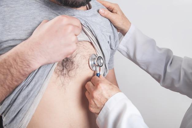 Arts die een stethoscoop gebruikt die geduldig hart controleert.