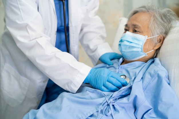 Arts die een stethoscoop gebruikt om de aziatische hogere vrouwenpatiënt te controleren die een gezichtsmasker draagt ter bescherming van het covid-19 coronavirus.