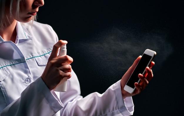 Arts die een telefoon met ontsmettingsmiddel desinfecteert