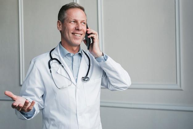 Arts die een telefoongesprek maakt