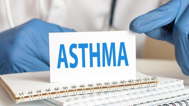 Arts die een witboekkaart met tekst houdt: astma