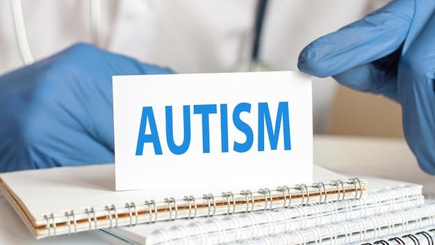 Arts die een witboekkaart met tekst houdt: autisme