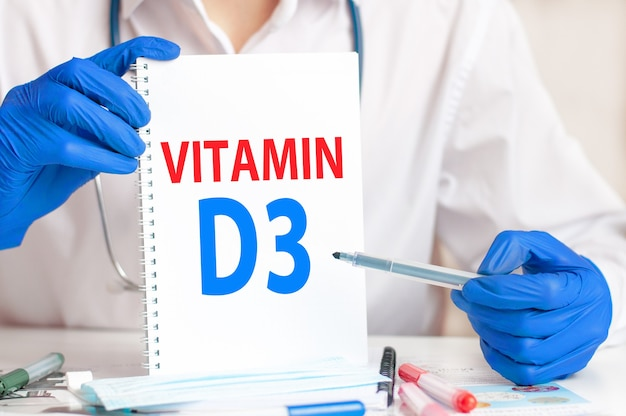 Arts die een witte kaart in handen houdt en het woord vitamine d3 wijst. gezondheidszorg conceptueel voor ziekenhuis, kliniek en medische zaken.