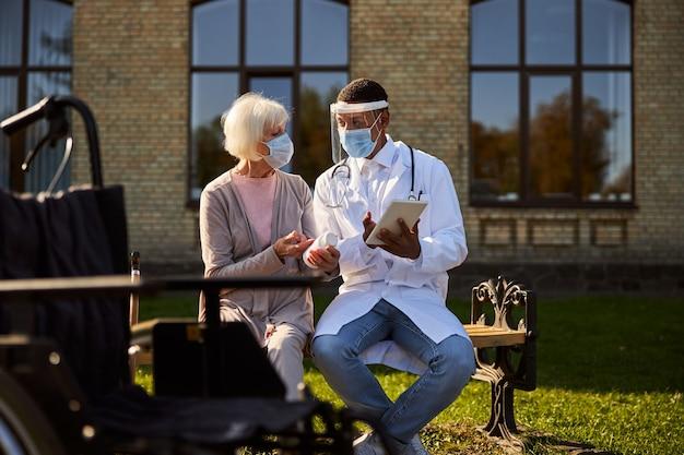 Arts die een witte ziekenhuisjas draagt en instructies geeft over medicijnen aan zijn patiënt terwijl hij een tablet in zijn handen houdt