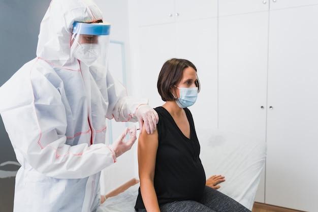 Arts die een zwangere vrouw een vaccin geeft tegen covid 19 of griep of kinkhoest