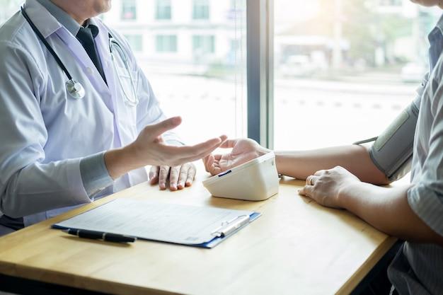 Arts die en bloeddruk van patiënt in het ziekenhuis, gezondheidszorgconcept meten controleren.