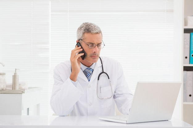 Arts die en computer telefoneert gebruikt