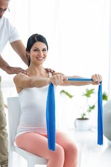 Arts die en fysiotherapie onderzoeken geven aan zwangere vrouw op oefeningsbal