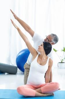 Arts die en fysiotherapie onderzoekt geeft aan zwangere vrouw