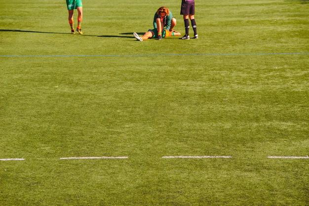 Arts die geblesseerde rugbyspeler bijwoont.