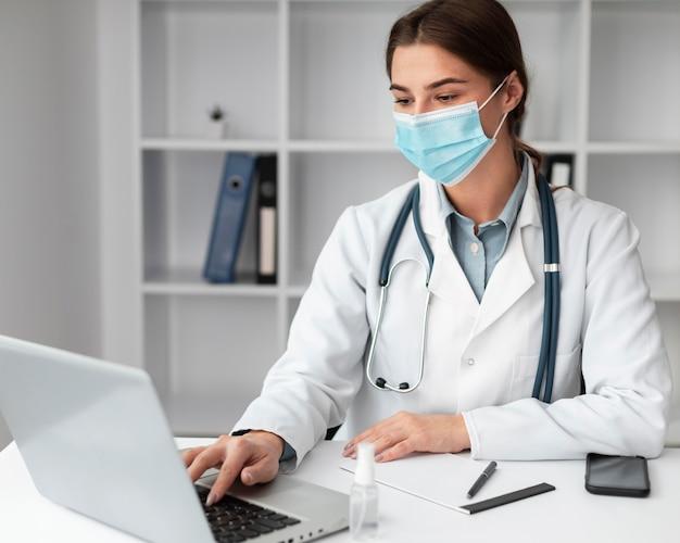Arts die gezichtsmasker draagt bij de kliniek
