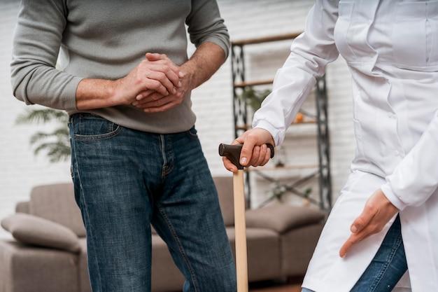Arts die haar patiënt laat zien hoe ze krukken moet gebruiken