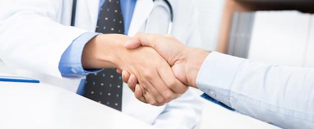 Arts die handdruk met patiënt in het bureau maakt