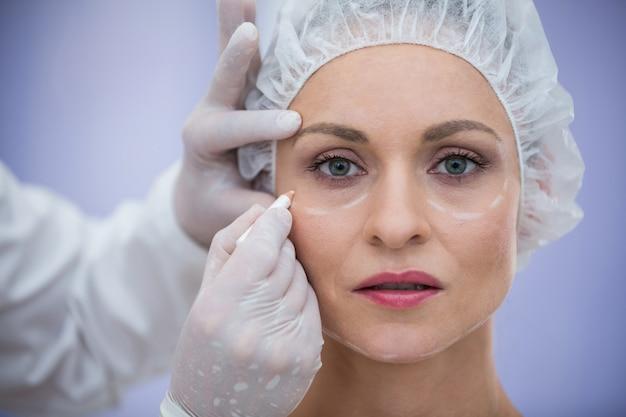 Arts die het gezicht van vrouwelijke patiënten voor kosmetische behandeling merken
