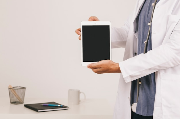 Arts die het scherm van het tablet op het kantoor toont