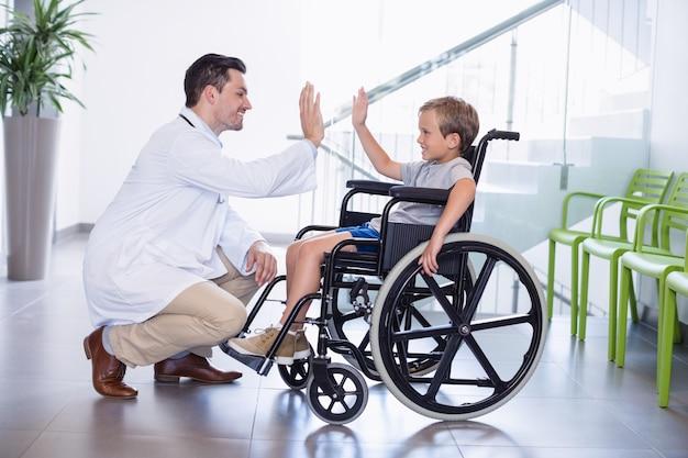 Arts die high five geeft om jongen uit te schakelen