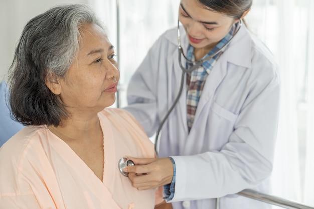 Arts die hogere bejaarde vrouwelijke patiënt in het bedpatiënten van het ziekenhuis onderzoeken - medisch en gezondheidszorg hoger concept