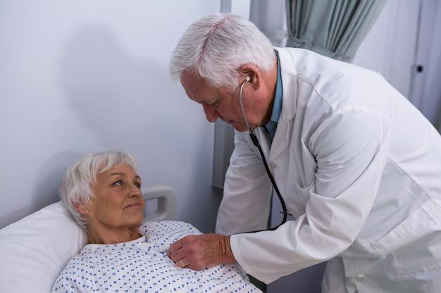 Arts die hogere patiënt met een stethoscoop onderzoekt