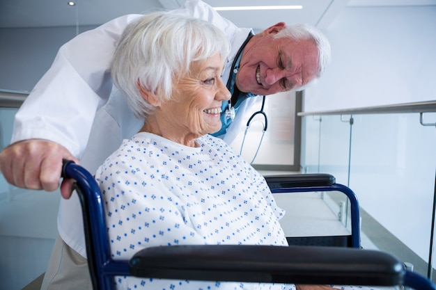 Arts die hogere patiënt op rolstoel in doorgang houdt