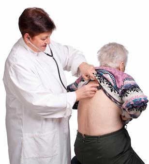 Arts die hogere vrouw op een witte achtergrond onderzoekt