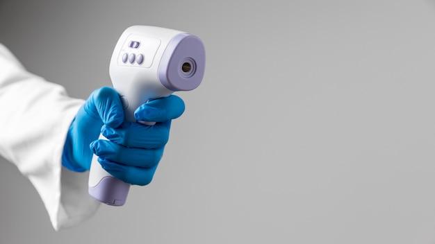 Arts die in handschoenen thermometer met exemplaarruimte houdt