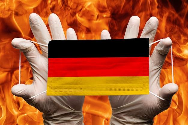 Arts die in witte handschoenen een medisch gezichtsmasker houdt, ademhalingsverband met de vlag van het nationale land van duitsland bovenop het masker. concept op de achtergrond van gevaarlijke rode vlammen natuurlijk vuur