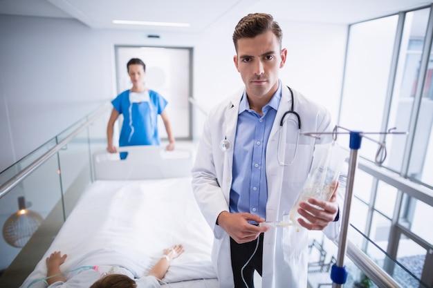 Arts die iv druppel aanpassen terwijl patiënt die op bed ligt