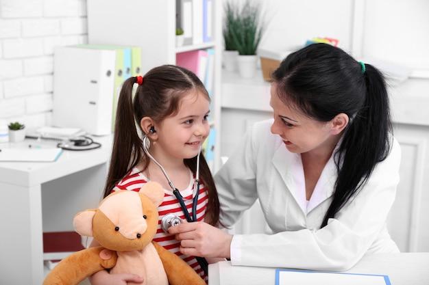 Arts die kind in het bureau onderzoekt