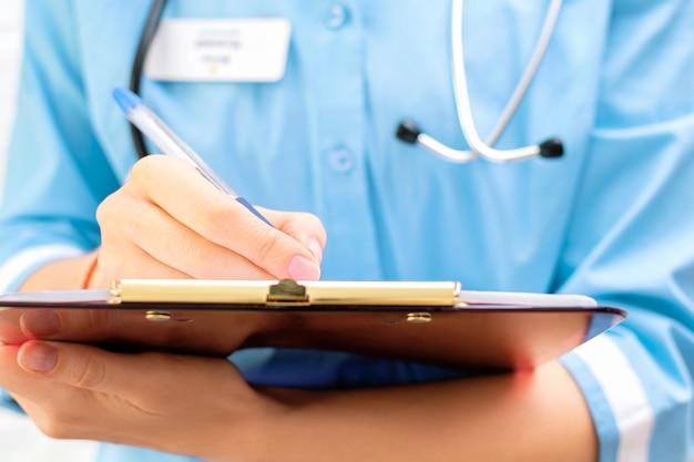 Arts die klembord vasthoudt en records schrijft diagnose in medische kaart patiëntgeschiedenis in het ziekenhuis