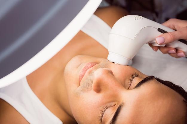 Arts die laserhaarverwijdering op geduldig gezicht uitvoert