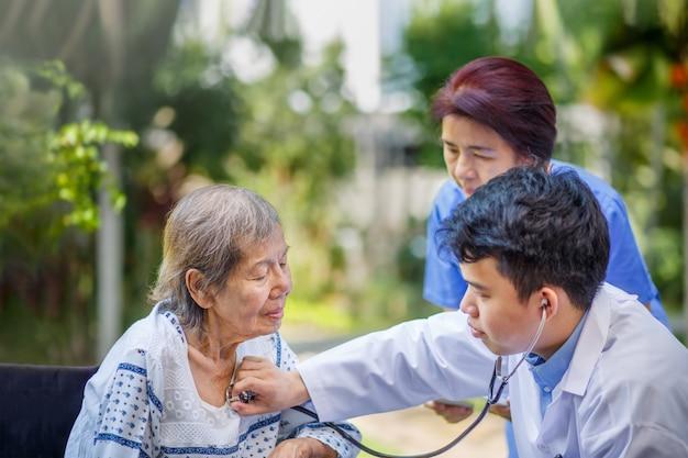 Arts die longen van bejaarde vrouw controleren tijdens medische thuiszorg