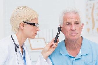 Arts die mannelijk patiëntenoor met otoscoop onderzoeken