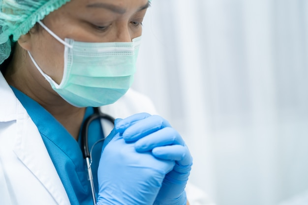 Arts die medisch masker en handschoenen met stethoscoop in het ziekenhuis draagt om het coronavirus covid-19 virus te beschermen.