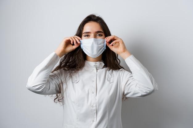 Arts die medisch masker op witte achtergrond draagt. jonge aantrekkelijke vrouw in medisch kleed. quarantaine coronavirus covid-19 trends.
