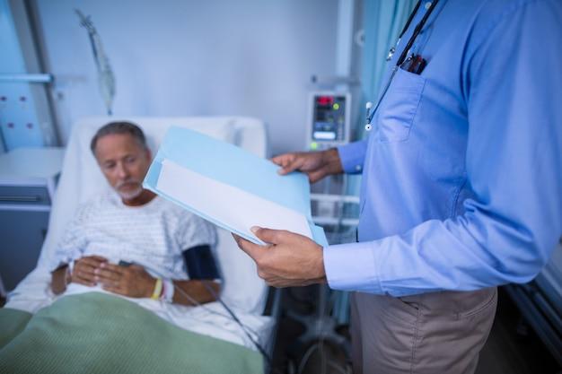 Arts die medisch rapport van patiënt controleert