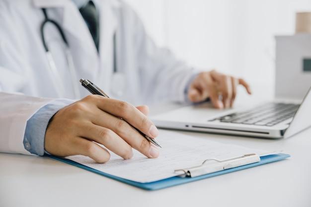 Arts die medische vorm opvult terwijl het zitten bij het bureau in het ziekenhuiskantoor. arts op het werk.