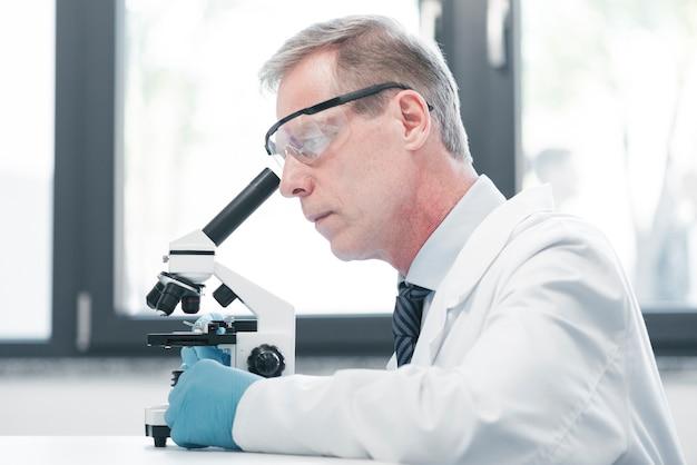 Arts die met een microscoop analyseert