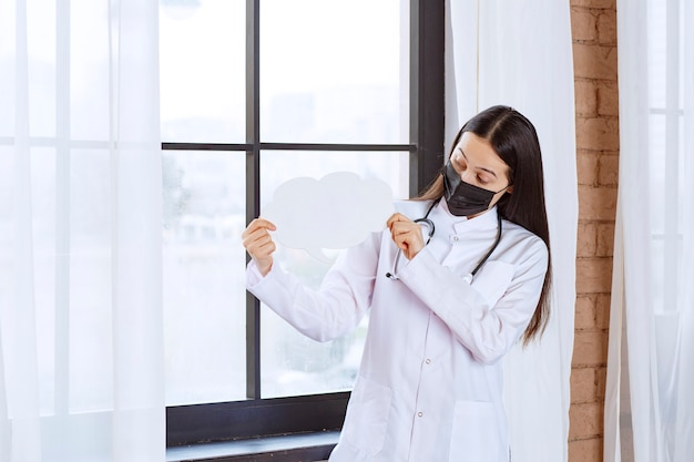 Arts die met een stethoscoop en een zwart masker een wit denkbord van de wolkenvorm houdt.