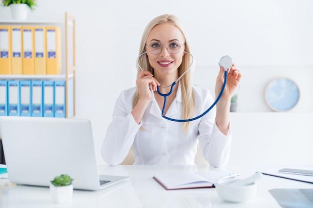 Arts die met een stethoscoop in haar kantoor werkt