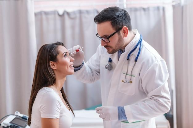 Arts die met ernstige gezichtsuitdrukking een monster met wattenstaafje uit het oog neemt.