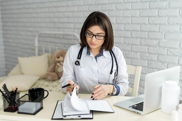Arts die met laptop computer werkt en op papierwerk schrijft. ziekenhuis achtergrond.