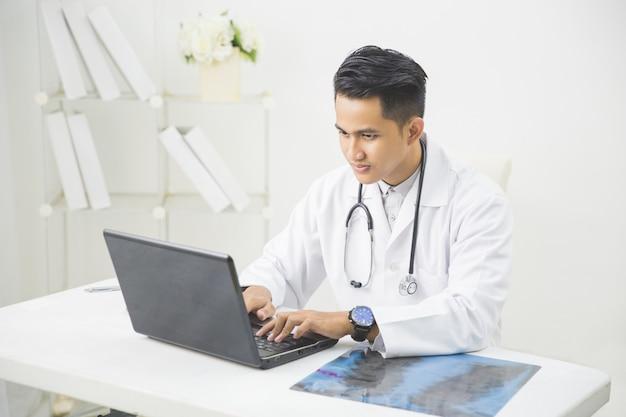 Arts die met laptop in het bureau werkt